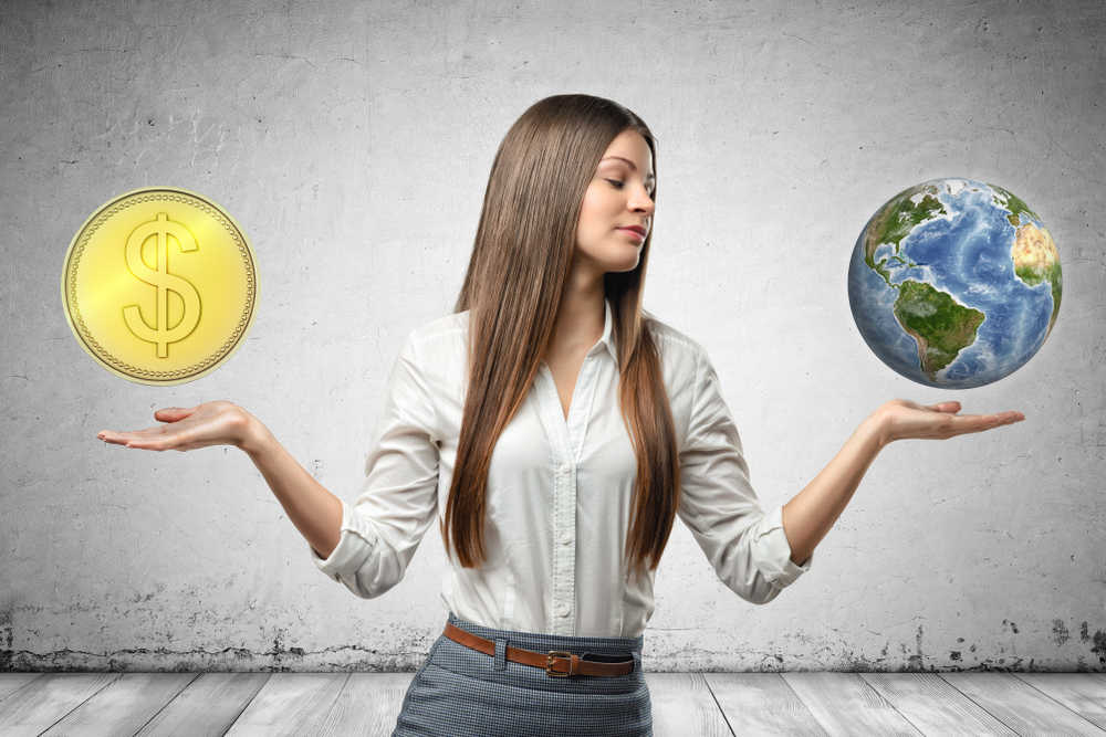 Business woman balancing profits (coins) and sustainability (earth)
